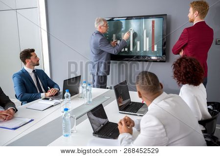 Director analyzing statistics at meeting with his manager
