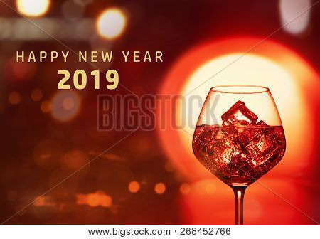 Wine Glasses And Happy New Year 2019 Greeting Over Red Bright Background. Happy New Year 2019