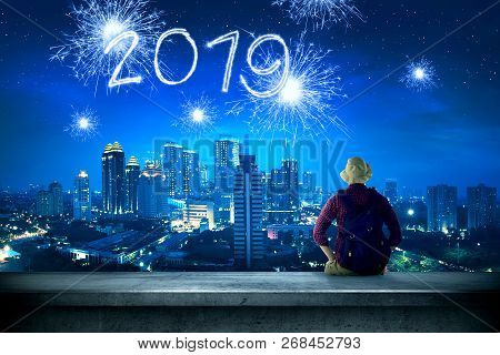 Rear View Of Asian Traveler Man Sitting On The Rooftop Looking At 2019 From Sparkling Fireworks On T