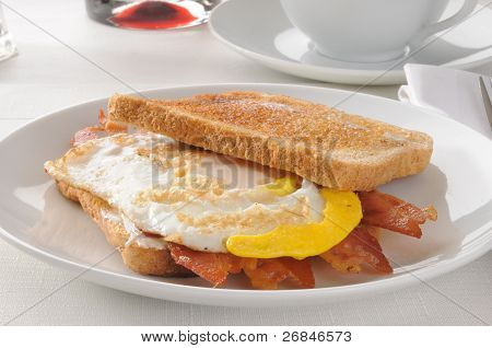 A bacan and fried egg sandwich on buttered toast poster