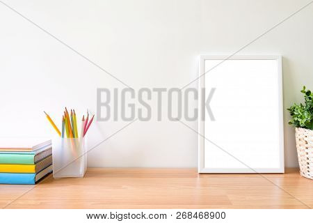 Mock Up Of Photo Frame On Wooden Table. Copy Space Of Working Table With Books Pencils And Blank Pho
