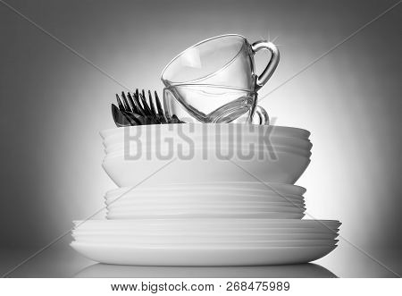 Clean Plates And Cutlery On A Bright Beautiful Gray Background