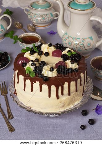 Delicious Cream Cake On The Table With A Tablecloth And Tea In A Beautiful Set