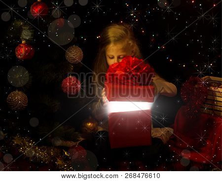 The Magic Of Christmas. The Little Girl In The New Year Location Looks In A Gift Box