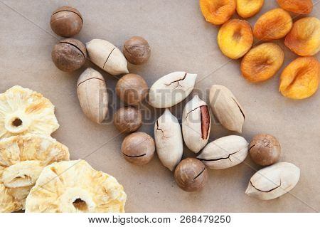 Macadamia, Brazil Nuts, Bertholletia, Pecan Dried Pineapples And Apricots On Brown Wrapping Paper. R