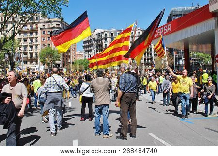BARCELONA, SPAIN - APRIL 15, 2018: Catalans wave flags at the Llibertat Presos Politics (Free Political Prisoners) march in support of politicians jailed after the independence declaration of 2017.