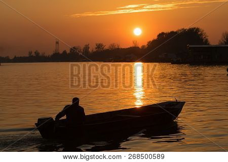 Fisherman In Nature In Sunset. People Lifestyle. Fisherman Silhouette On The River In Sunset. People