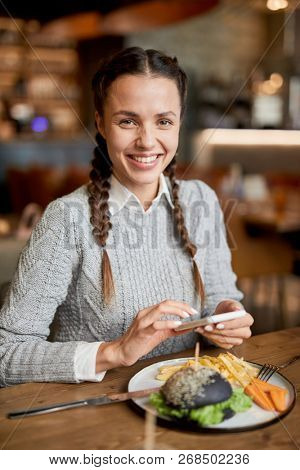 Happy girl in casualwear looking at you while sitting by table in cafe and texting in smartphone
