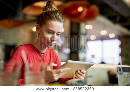 Contemporary young female blogger with tablet siting in cafe and recording video for her internet channel subscribers