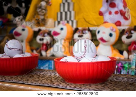 Close-up Of Baseball Balls For The Game Of Throw At Jars In A Fair. In The Background The Jars And T