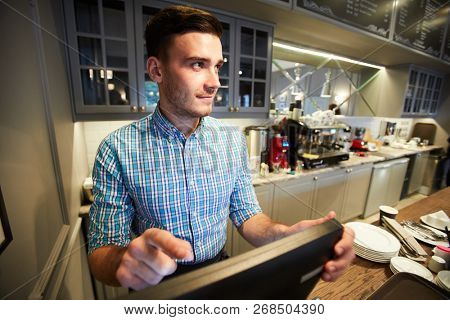 Young sales clerk standing by counter in front of computer and entering order information