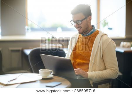 Happy young blogger with laptop sitting in cafe and browsing in the net by cup of coffee