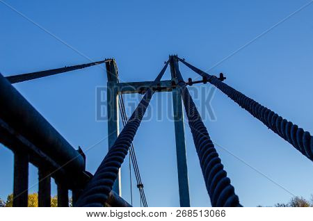 Cable-stayed bridge with large steel cables, close-up in the evening during the dawn against the sky, clouds and sunlight. poster