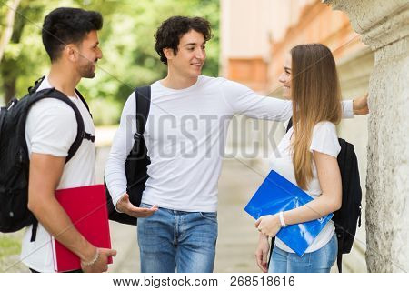 Three students talking to each other outdoor in a college courtyard