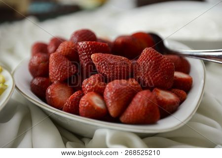 White Ceramic Pot With Clean Strawberries Inside.