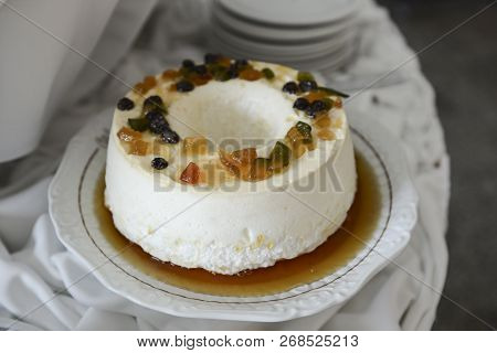 Egg White Pudding With Sugar Syrup And Dried Fruit On An Ornate Round Dish.