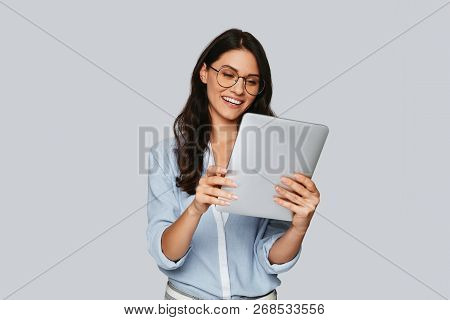 Examining Her New Tablet. Attractive Young Woman Working Using Digital Tablet And Smiling While Stan