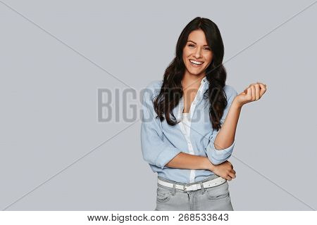 Portrait Of Confidence. Attractive Young Woman Looking At Camera And Smiling While Standing Against