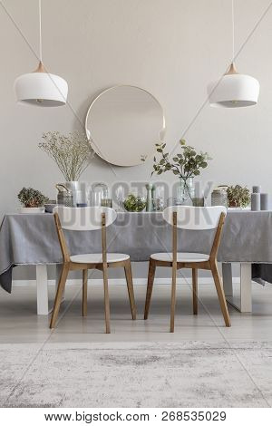 White Chairs At Table In Elegant Dining Room Interior With Round Mirror And Lamps. Real Photo