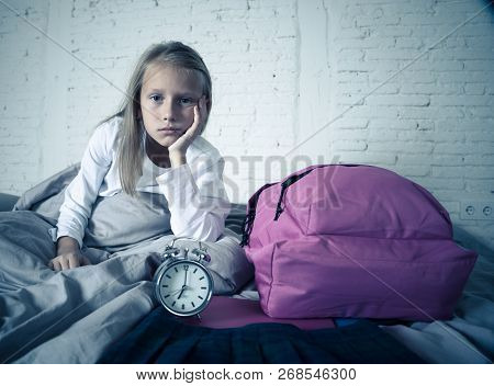 Beautiful Blonde Little Girl Sad Sleepless And Angry Showing Alarm Clock Time To Get Ready For Schoo