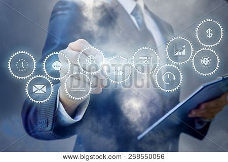 A Businessman Is Operating With The Cogwheel Mechanism Containing Icons And Symbols While Making Not