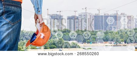 An Engineer With A Building Helmet In His Hand Is Standing Opposite The Set Of City Skyscrapers. The