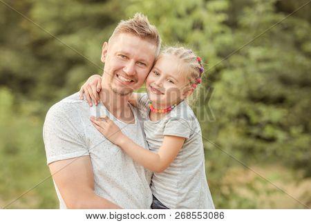 Happy dad holding smiling little daughter hugging