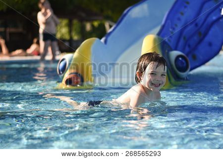 Little Boy Play Swimming And Playing In The Pool. Cheerful Child Play In The Swimming Pool