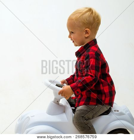 Easy To Ride. Little Child Ride On Toy Car. Boy Child On Riding Toy. Little Baby Enjoy Playing In Ki