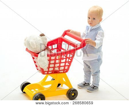 Happy Childhood And Care. Little Boy Child In Toy Shop. Shopping For Children. Savings On Purchases.