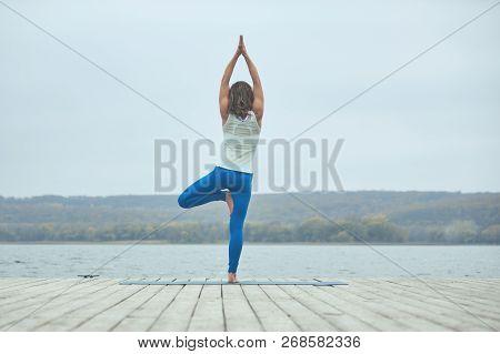 Beautiful Young Woman Practices Yoga Asana Parshva Vrikshasana - Tree Pose On The Wooden Deck Near T