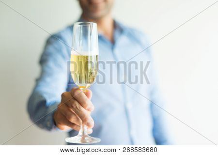 Close-up Of Man Saying Toast And Raising Champagne Flute. Unrecognizable Man Drinking Alcohol At Par