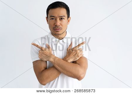 Serious Young Man Crossing Arms And Pointing Index Fingers To Different Directions. Confused Mix Rac
