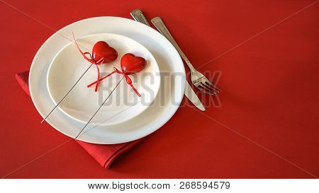 Valentines Day Table Setting With Two Hearts Fork And Knife Tablecloth On Red Background. Romantic T