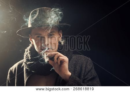 Man In Coat, Hat Smoking Cigar, Dark Background. Macho On Mysterious Face, Detective, Investigator,