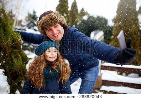 Beautiful Dad And Daughter Doing Selfie With Freshly Cut Christmas Tree With Smartphone Near Home. Y