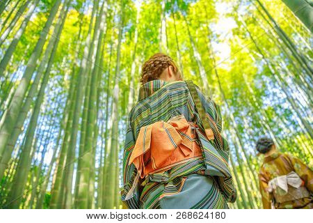 Hanami In Spring Season With Unidentifiable Women With Green Japanese Kimono In Bamboo Grove Of Take