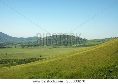 Minimalistic Green Landscape With Diagonal Side Of Hill On Foreground, Beautiful Rocky Hills And Cle