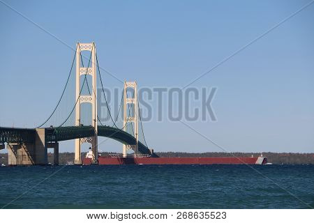 A Great Lakes Freighter Passing Underneath The Mackinac Bridge At The Straits Of Mackinac