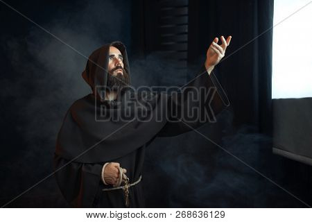 Medieval monk praying against a window with light