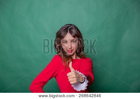 Smiling Attractive Woman In Red Dress Is Posing With Hand On Hip And Showing Thumb Up On Green Turqu