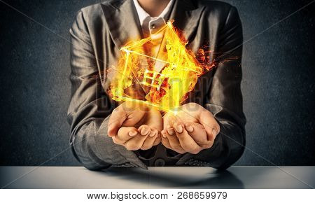 Closeup Of Businessman In Black Suit Keeping Flaming House Symbol In Hands With Dark Wall On Backgro