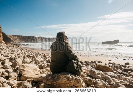 A Girl With A Backpack Or A Tourist Or A Traveler In Solitude Admires A Beautiful View Of The Atlant
