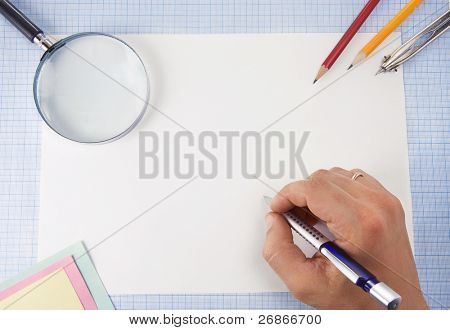 male hand writing by pen and magnifying glass on graph grid paper