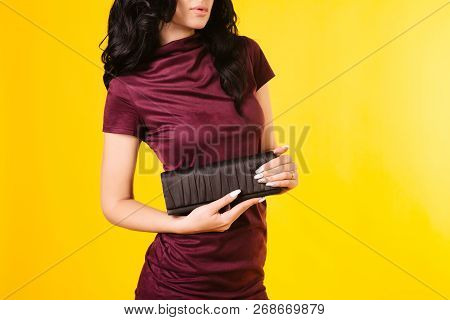 Young Woman In A Burgundy Dress Holding A Purse On A Yellow Background.
