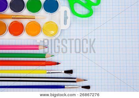 pencils, felt pens, paint brush and scissors on graph grid paper
