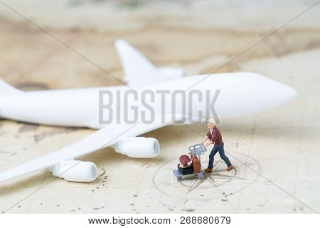 Traveller and transportation concept, miniature adult man with airport cart and luggage with toy airplane on vintage world map with compass, next destination, new business journey. poster