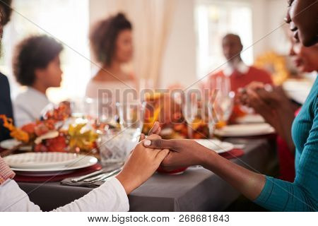Young black adult woman and her daughter holding hands and saying grace with their multi generation family at the Thanksgiving dinner table, detail, focus on foreground