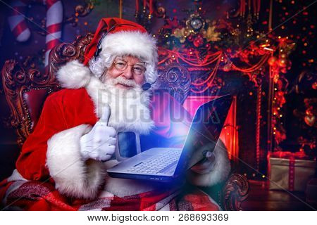A portrait of Santa Claus sitting at his home with a laptop. Miracle time. Christmas, New Year.