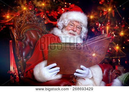 A portrait of Santa Claus sitting at his home with photo album. Miracle time. Christmas, New Year.